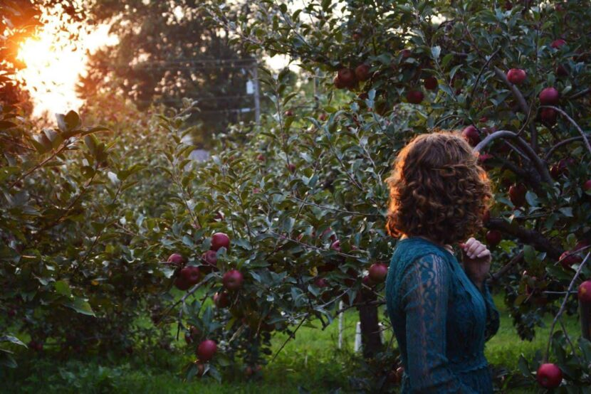 photo of woman walking in an orchard