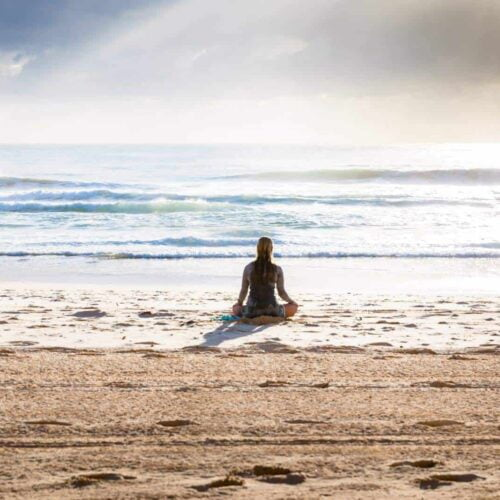 Photo of woman meditating on beach