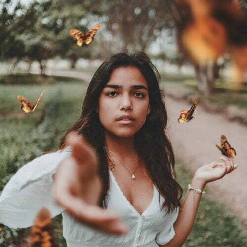 photo of woman releasing butterfly to symbolise letting go of trauma